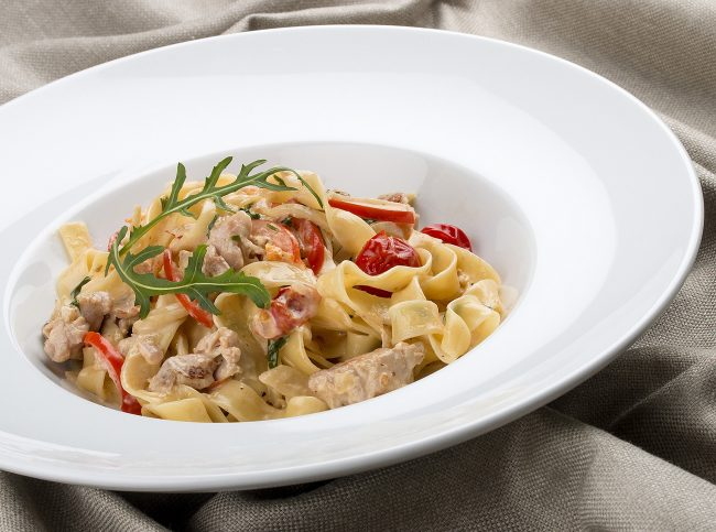 Tagliatelle with rabbit and pepper, with cream sauce in a white